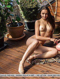 Slava bares her slender body with beautiful tits as she waters the plants.