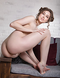 Alluring Ginger Frost bares her slender, creamy body and trimmed pussy on the sofa.