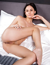 Sade Mare strips on the bed baring her slender body and tight ass.