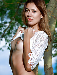 Maddison flaunts her tight body and shaved pussy as she poses on the grassy field.