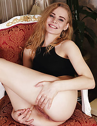 Gorgeous blonde Ellie displays her delectable pussy on the chair.