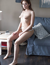 Keira Blue flaunts her puffy nipples and smooth pussy on the couch.