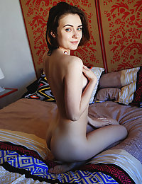 Alice Shea displays her small, creamy body and pink pussy on the bed.