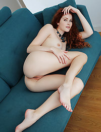 Redhead Adel C shows off her smoking hot body as she strips on the couch.